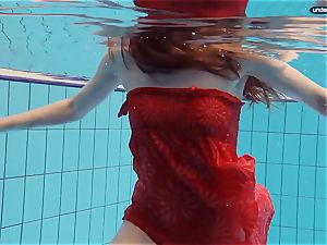 red clothed teen swimming with her eyes opened